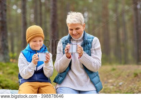 picking season, leisure and people concept - grandmother and grandson having picnic and drinking tea in autumn forest