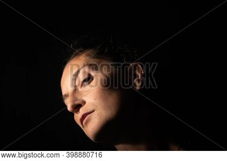 Dark Profile Portrait Of A Very Dimly Lit Woman. The Woman Has Her Head Raised And Is Looking Straig
