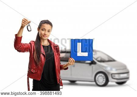 Female driver with a urban car holding a key and a learner plate isolated on white background
