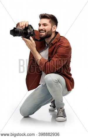 photography, profession and people and concept - happy smiling man or photographer with digital camera staying on one knee and taking picture over white background