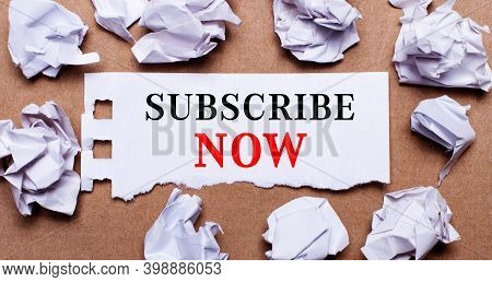 Subscribe Now Written On White Paper On A Light Brown Background.