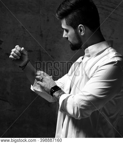 Black And White Portrait Of Handsome Bearded Brutal Muscular Man With Tattoo On Forearm Putting On W