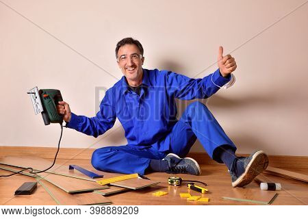 Professional Parquet Assembler With Ok Gesture And Cutting Machine In Hand Sitting On The Floor Asse