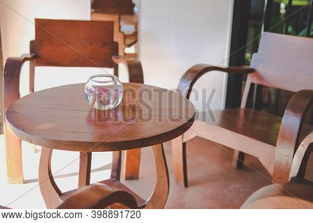 Glass Bowl With Flower Floating On Water Decorating On Wooden Table In Living Room At Home