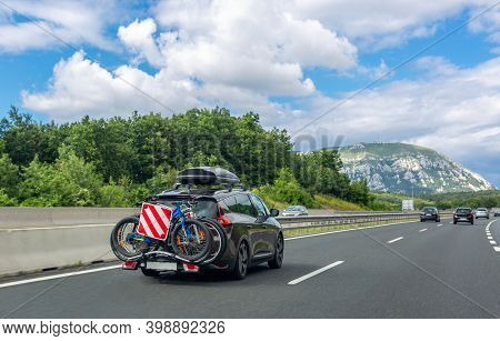 Black Car With Roof Luggage Box And Trunk Bike Rack Driving On Highway. Beautiful Mountain Landscape
