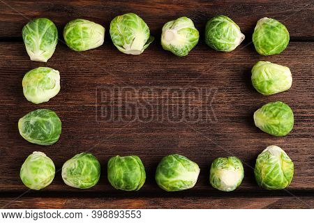 Frame Made With Brussels Sprouts On Brown Wooden Table, Flat Lay. Space For Text