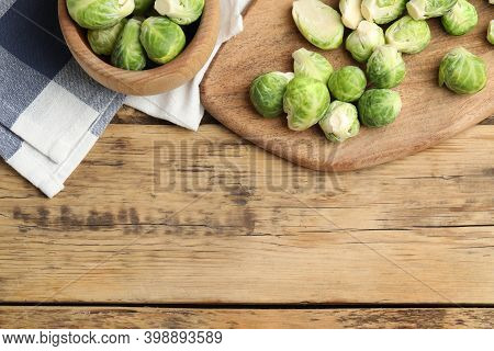 Fresh Brussels Sprouts On Wooden Table, Flat Lay. Space For Text