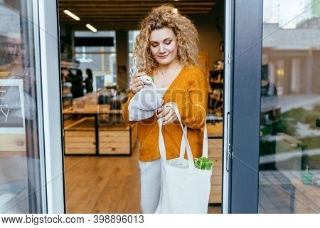 Blond Curly Lady In Yellow Cardigan Comes Out Of Doorway Of Local Grocery Store. Trendy Woman Use Re