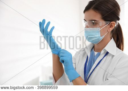 Doctor In Protective Mask And Glasses Putting On Medical Gloves Against Light Background