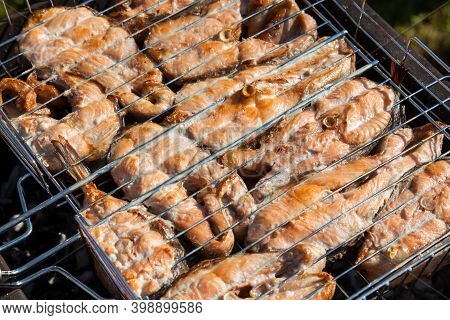 Top View Of The Browned Steaks Of Red Coho Salmon Fried On Charcoal In A Barbecue On A Summer Day In