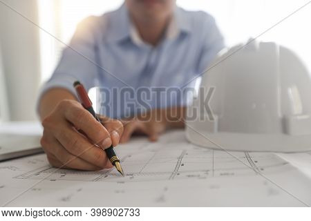 Young Engineers Or Architect Holding Pen And Drawing Plan On Blueprint In Working Site.