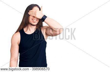 Young adult man with long hair wearing goth style with black clothes smiling and laughing with hand on face covering eyes for surprise. blind concept.
