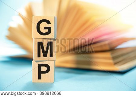 Gmp Good Manufacturing Practice - Inscription On Wooden Cubes On The Background Of An Open Book.
