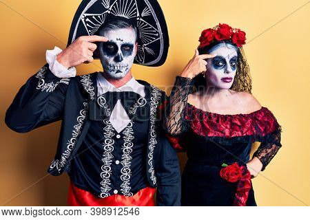 Young couple wearing mexican day of the dead costume over yellow pointing unhappy to pimple on forehead, ugly infection of blackhead. acne and skin problem