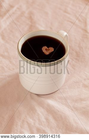 White Cup Of Coffee With Heart Shaped Sugar On Pink Textile Background. Concept Of Love