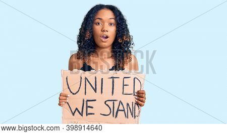 Young african american woman holding united we stand banner scared and amazed with open mouth for surprise, disbelief face
