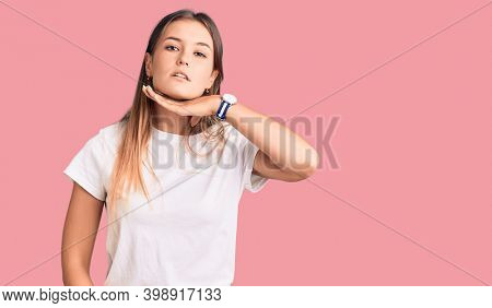 Beautiful caucasian woman wearing casual white tshirt cutting throat with hand as knife, threaten aggression with furious violence