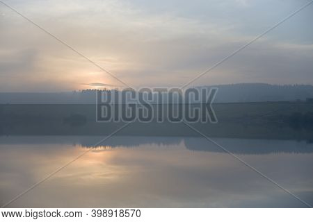 Calm Reservoir Water Reflects Misty Sunset. Serene Horizontal Landscape Image With Blue And Orange P
