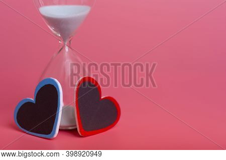 Two Hearts And An Hourglass On A Pink Background.