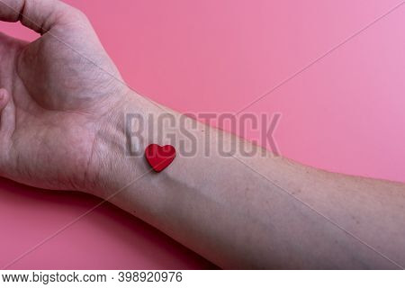 Heart On The Wrist Of A Man's Hand On A Pink Background.