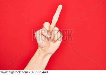 Hand of caucasian young man showing fingers over isolated red background showing provocative and rude gesture doing fuck you symbol with middle finger