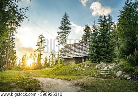 Isolated Cabin In Mountains Surrounded By Deep Forrest, Sunset In Background With Sunrays. Slovakia