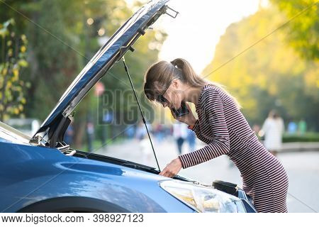 Young Upset Woman Driver Talking On Mobile Phone Near A Broken Car With Open Hood Waiting For Help H