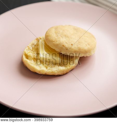 Homemade Flaky Buttermilk Biscuit On A Pink Plate On A Black Background, Low Angle View. Close-up.