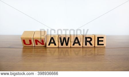 Aware Or Unaware Symbol. Turned A Cube And Changes Words 'unaware' To 'aware'. Beautiful Wooden Tabl