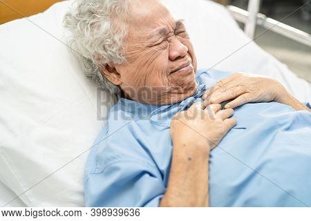 Asian Senior Or Elderly Old Lady Woman Patient Feel Pain In The Chest And Heart On Bed In Nursing Ho