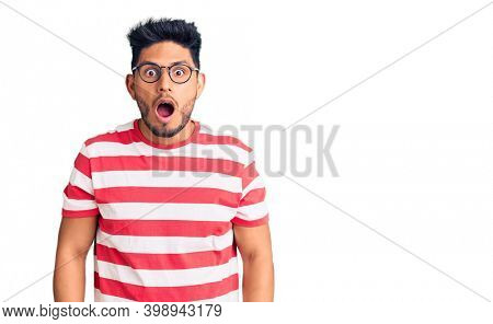 Handsome latin american young man wearing casual clothes and glasses afraid and shocked with surprise and amazed expression, fear and excited face.