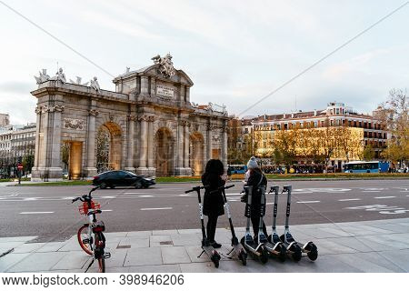 Madrid, Spain - December 6, 2020: People Beside Rental Scooters In Plaza De La Independencia Or Inde