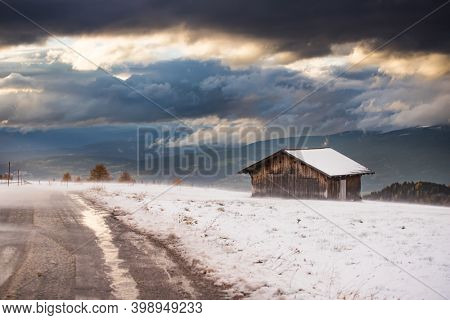 Small cottage in magic sunset in Dolomite mountains, Alpe di Siusi, Italy in winter