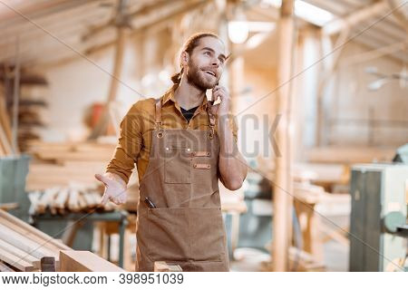 Handsome Carpenter Talking On Phone, Having A Brake During The Woodwork In The Workshop