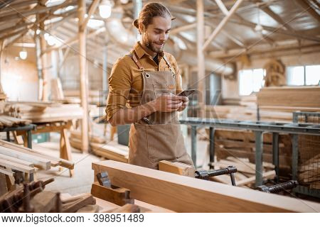 Portrait Of A Handsome Carpenter Standing With A Smart Phone, Having A Brake During The Woodwork In