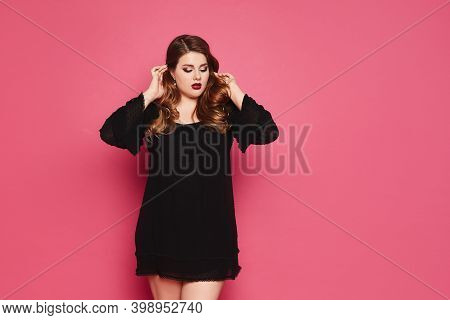 Plus-size Model Girl With Bright Makeup And Full Red Lips In A Short Black Dress Corrects Her Hair A