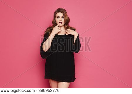 Confused Plump Woman With Bright Makeup In Short Black Dress Posing At The Pink Background, Isolated