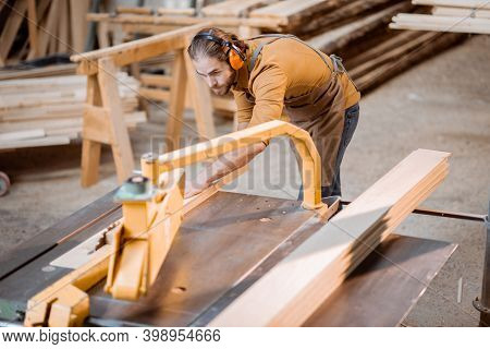 Carpentry Worker Sawing Wooden Planks With Circular Saw In The Joinery Warehouse
