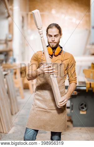 Handsome Carpenter In Uniform Working With Wood, Checking The Quality Of The Wooden Baluster At The