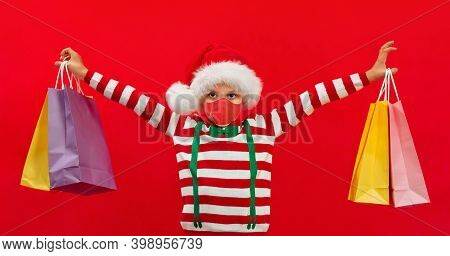 An African-american Boy In A Santa Hat And With Carrier Bags Holds Gifts In His Hands For Friends
