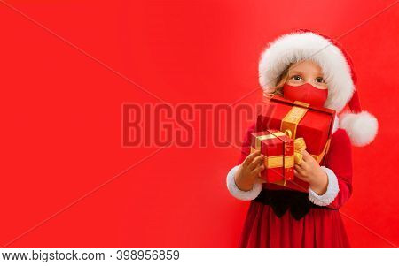 Funny Child In Santa Red Hat And Face Mask Holding Christmas Gift In Hand.