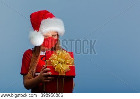 A Surprised Baby Girl In A Red Santa Hat And A Face Mask Holds A Christmas Gift In Her Hand.
