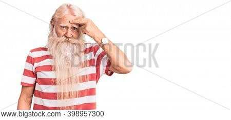 Old senior man with grey hair and long beard wearing striped tshirt pointing unhappy to pimple on forehead, ugly infection of blackhead. acne and skin problem
