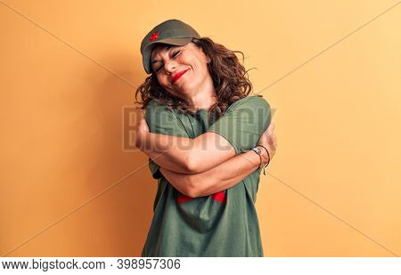 Middle age brunette woman wearing t-shirt and cap with red star symbol of communism hugging oneself happy and positive, smiling confident. Self love and self care