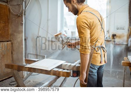 Worker Painting Wooden Product With A Spray Gun At The Painting Shop Of The Carpentry