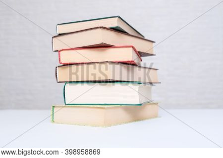 A Stack Of Books Lying On A White Table, Reading And Education Concept.