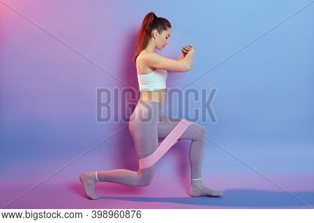 Dark-haired Woman In Sporty Top And Leggins, Makes Lunges With Sport Fitness Rubber Bands Isolated O