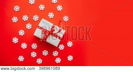 Gift Box Wrapped In Craft Paper With Red Ribbon Bow, Christmas Snow And Copyspace On A Red Backgroun