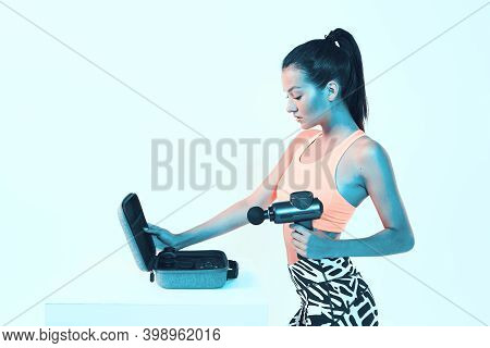Percussion Massager, Athletic Young Fit Female Posing With Handheld Massaging Gun In Neon Studio Lig