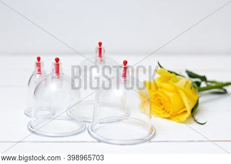 Jars For Hijama On A White Wooden Background And Yellow Flowers. Bloodletting. Sunnah Treatment. Isl